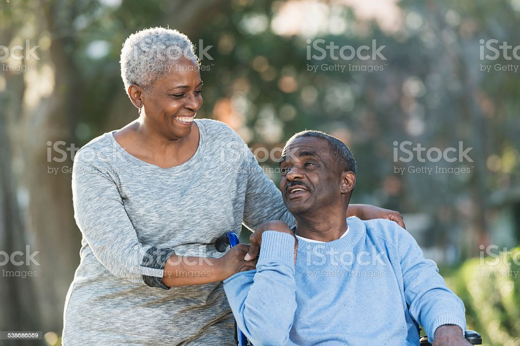 Senior couple with man in wheelchair stock photo