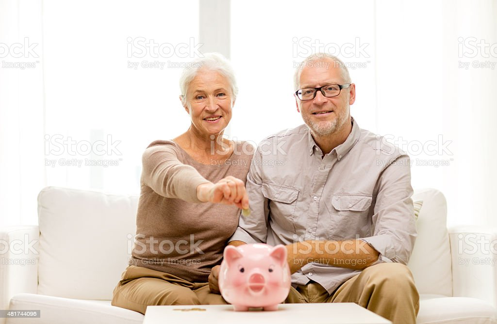senior couple with money and piggy bank at home stock photo
