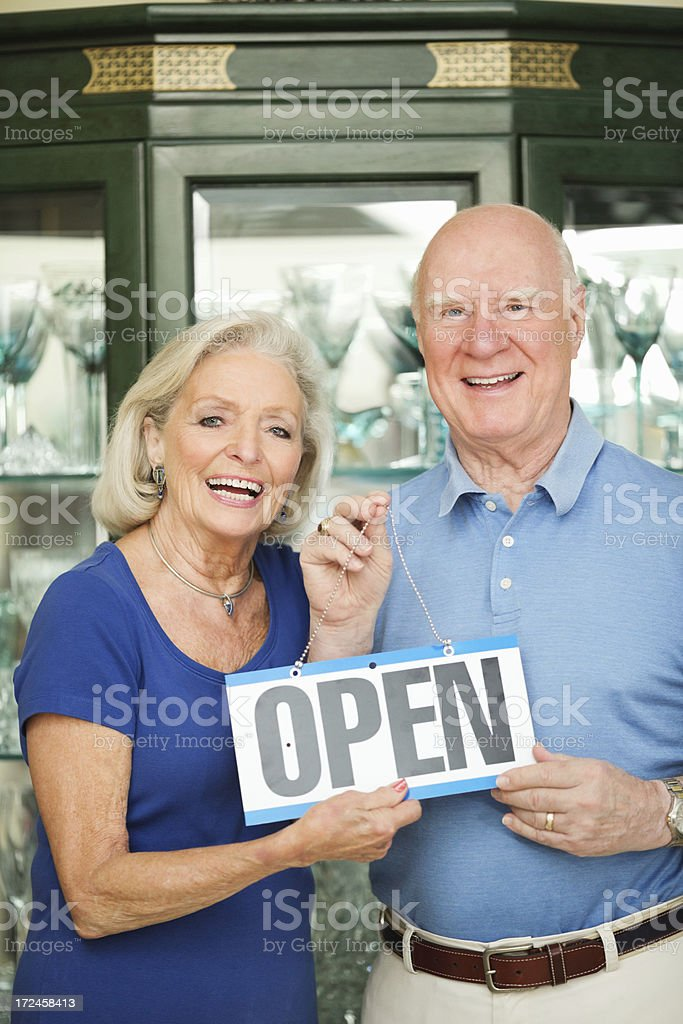 Senior Couple With Open Sign In Store royalty-free stock photo