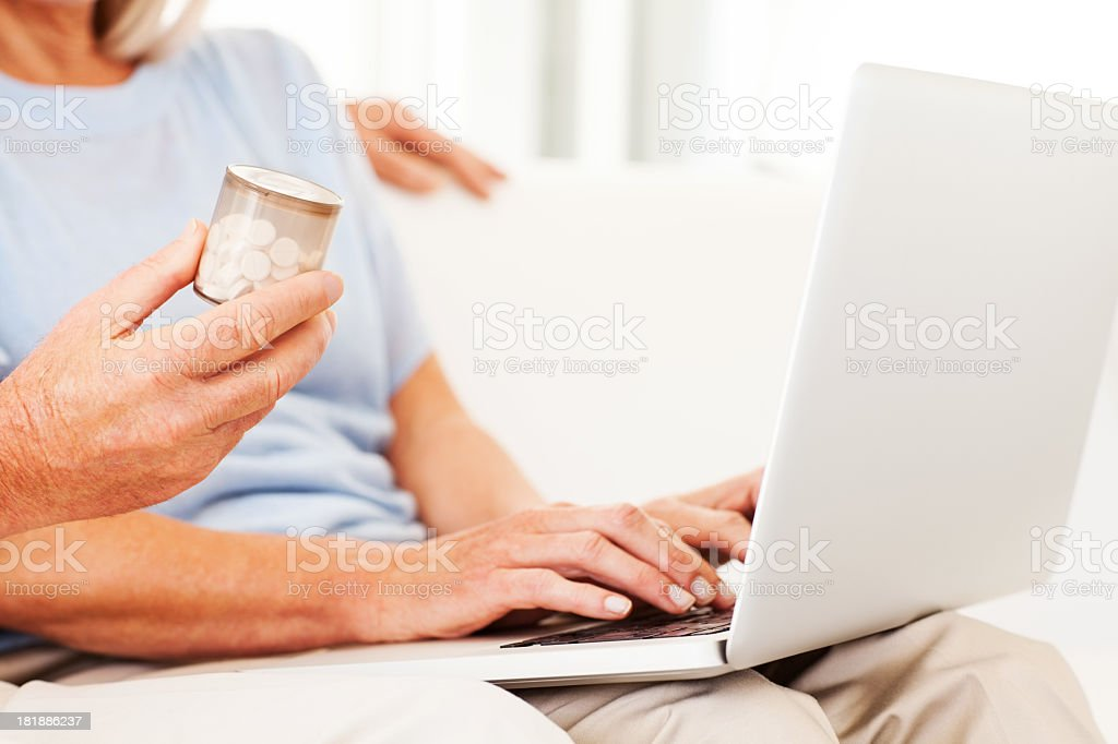 Senior Couple With Pill Bottle Using Laptop royalty-free stock photo