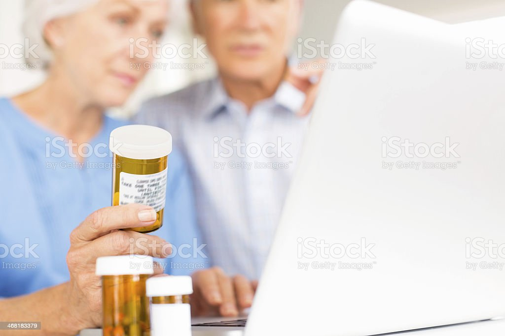Senior Couple With Pill Bottles And Laptop. royalty-free stock photo