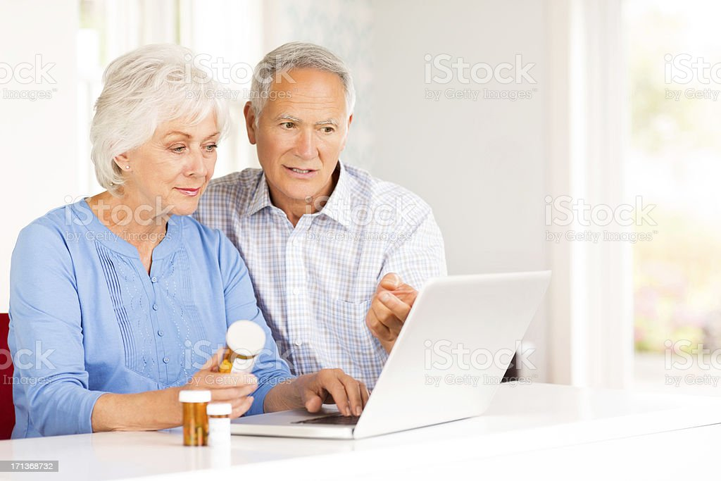 Senior Couple With Pill Bottles Browsing Internet On Laptop. stock photo