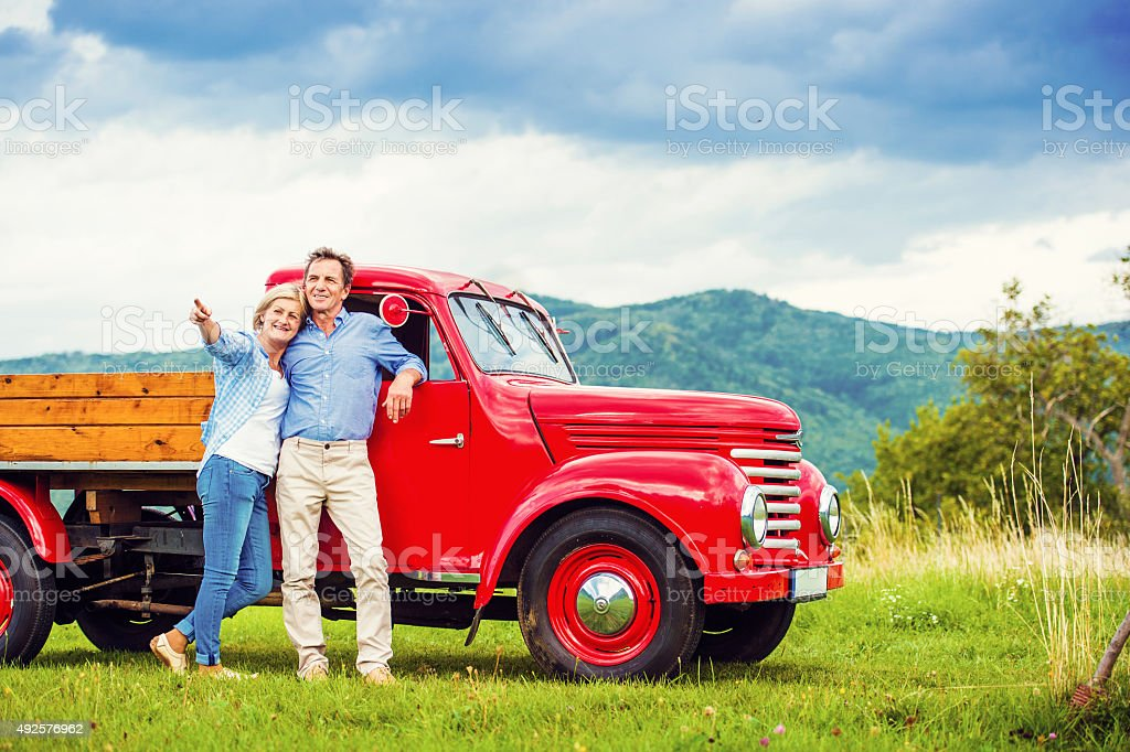 Senior couple with red car stock photo