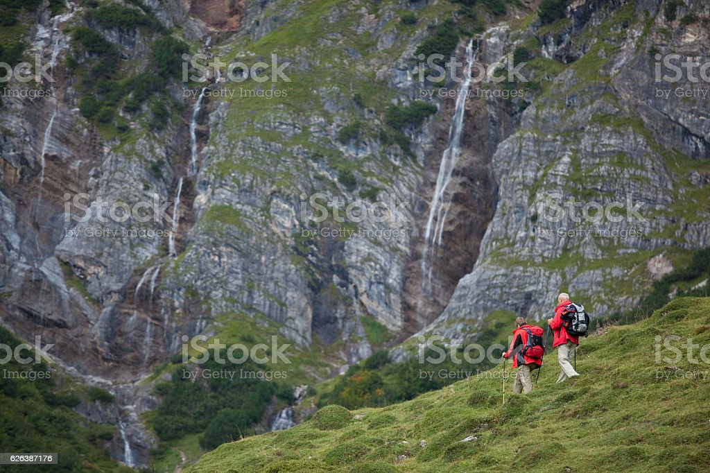 senior couple with red jackets hiking stock photo