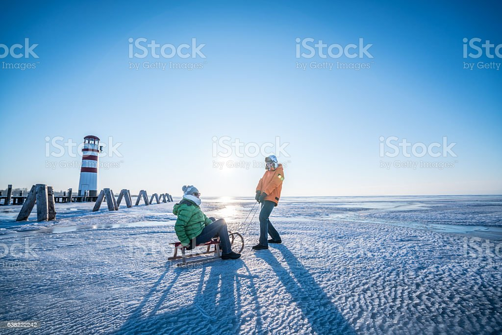 senior couple with sled on frozen lake neusiedl in backlight stock photo