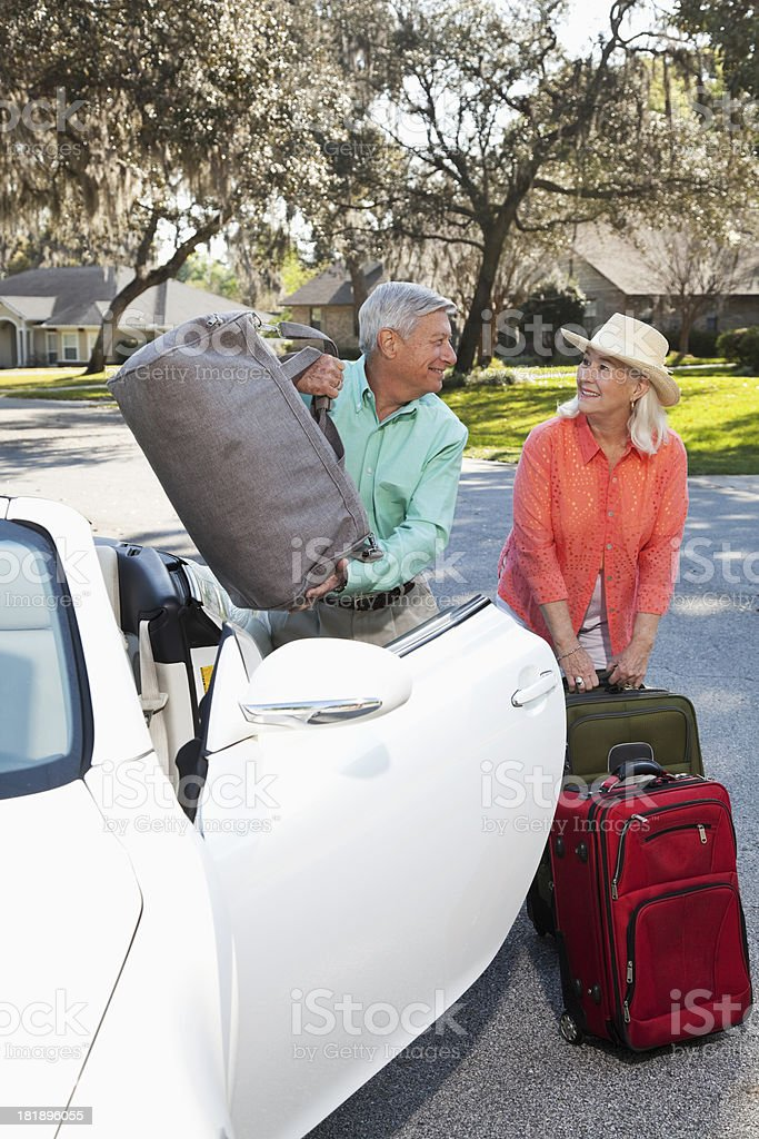 Senior couple with suitcases and convertible royalty-free stock photo