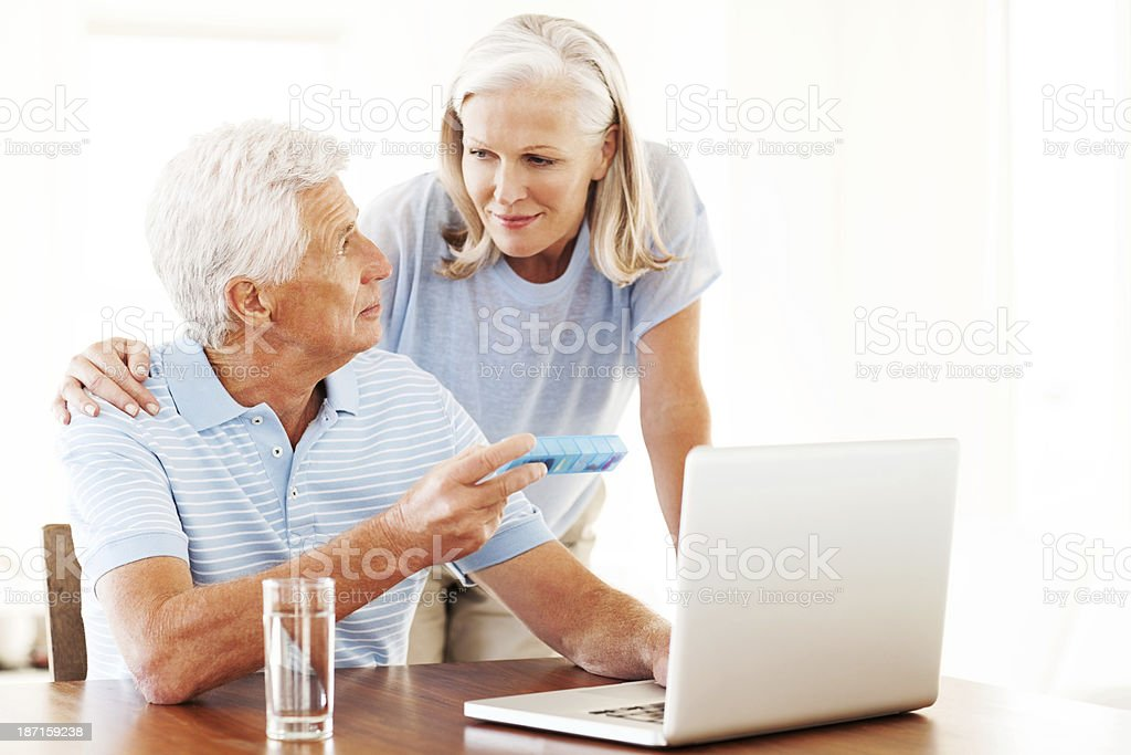 Senior Couple With Tablet Box Using Laptop stock photo