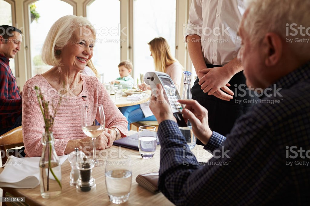 Senior Couple With Waiter Paying Bill In Restaurant stock photo