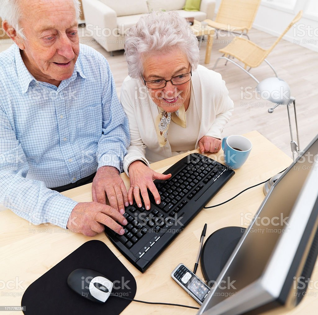 Senior couple working together on computer stock photo