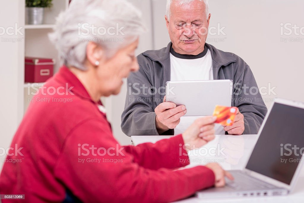 Senior couple working with computer stock photo
