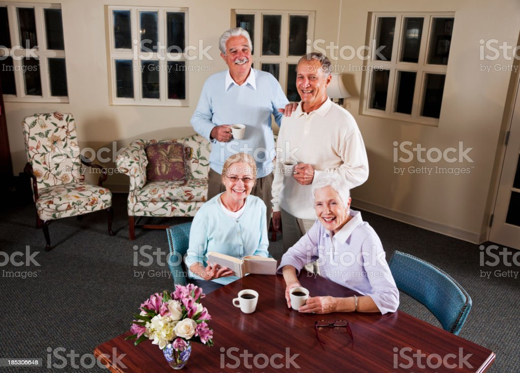 Senior couples drinking coffee in living room stock photo