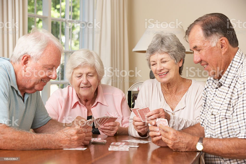 Senior Couples Enjoying Game Of Cards At Home stock photo