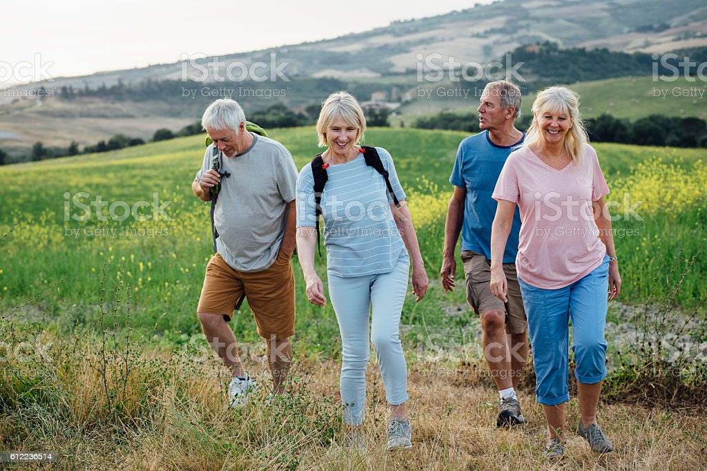 Senior Couples Outdoors Walking with a Backpack stock photo