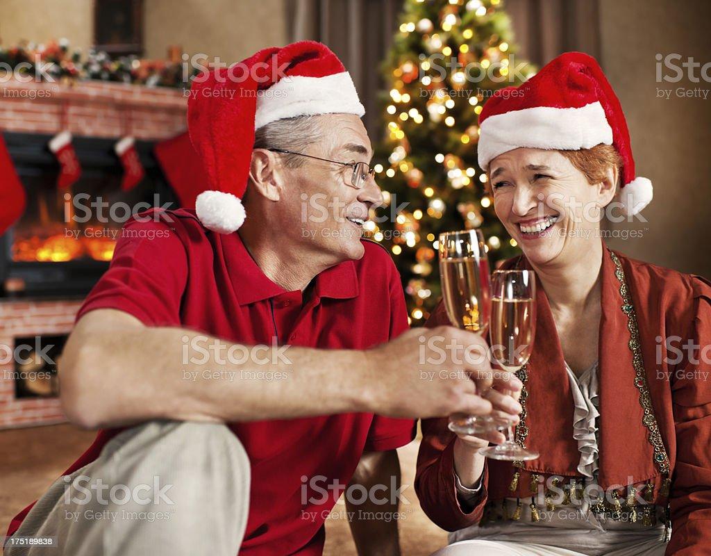 Senior couples wearing Santa's hats enjoying in champagne. royalty-free stock photo