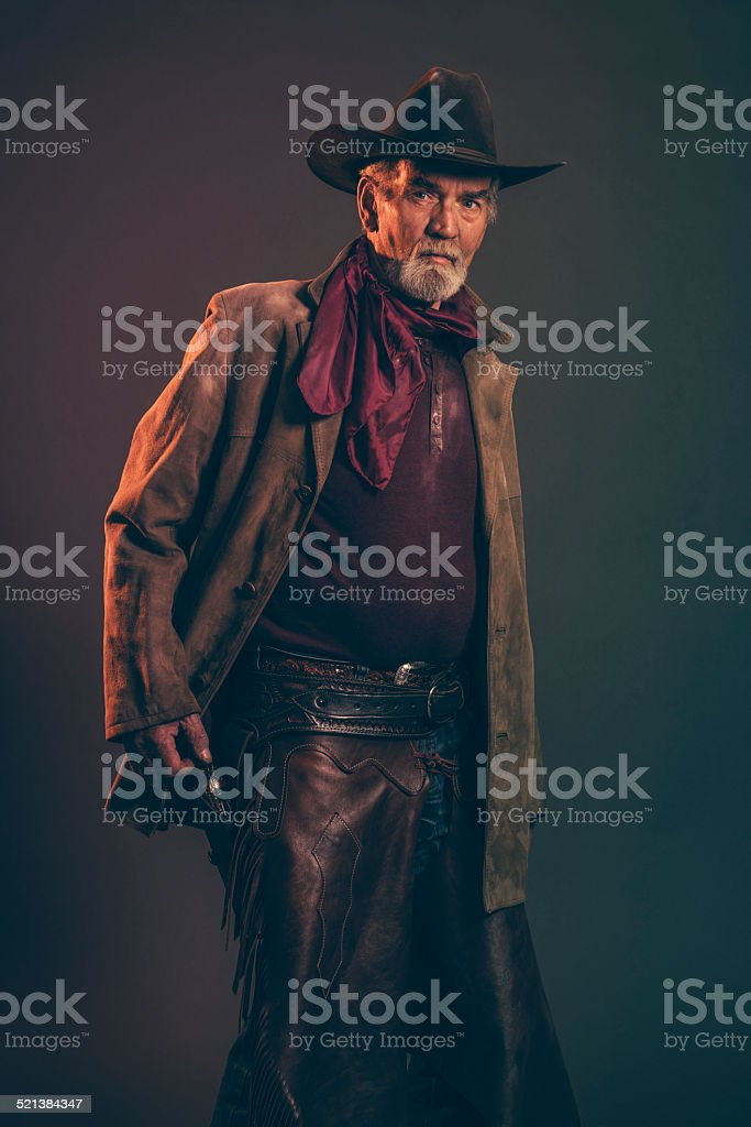 Senior cowboy with gray beard and brown hat pulling revolver. stock photo