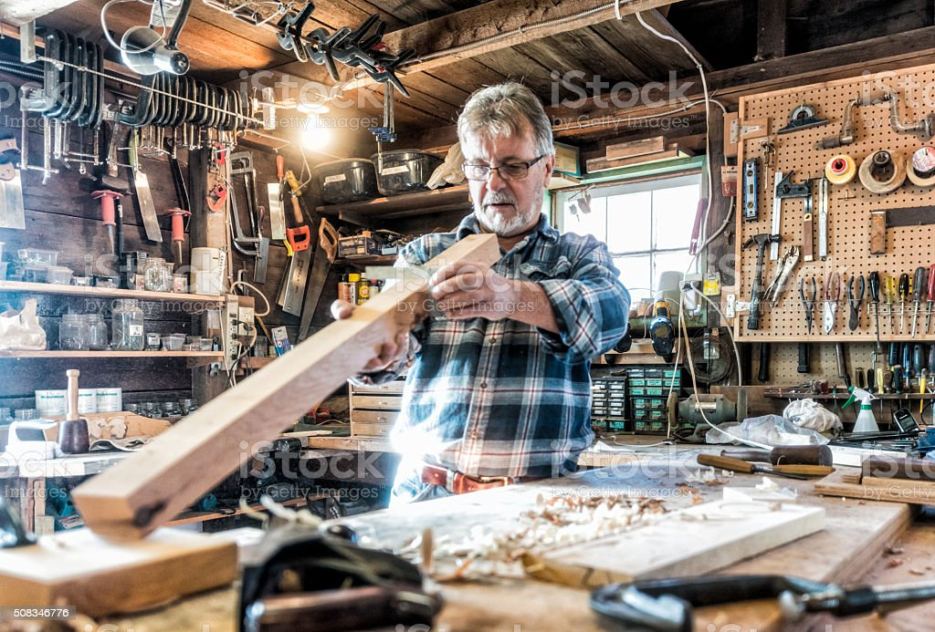 Senior craftsman working in traditional workshop stock photo