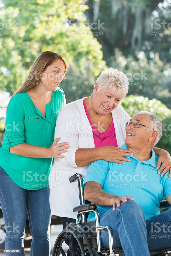 Senior cuople, man in wheelchair, with adult daughter stock photo