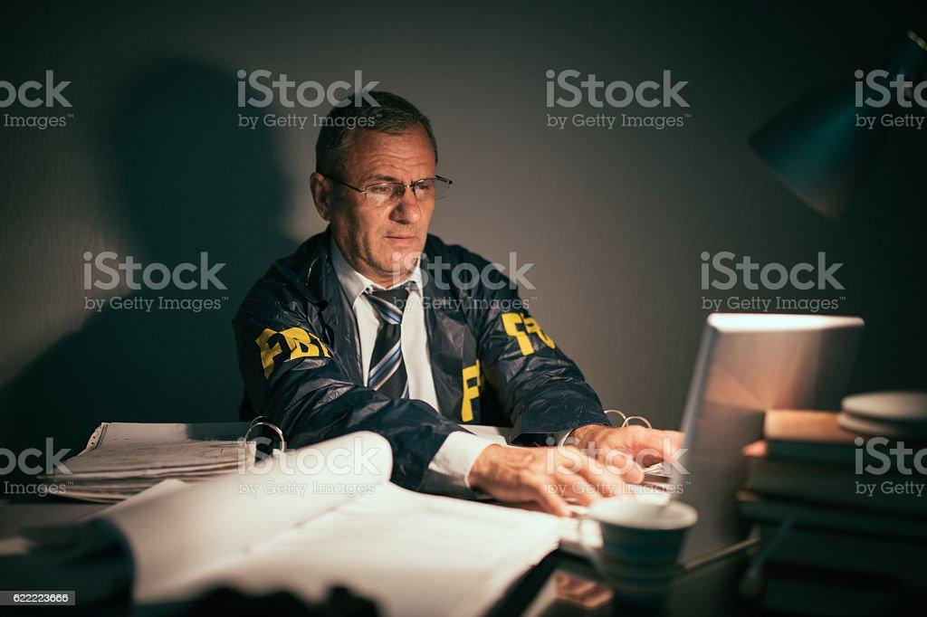 Senior detective working late hours stock photo