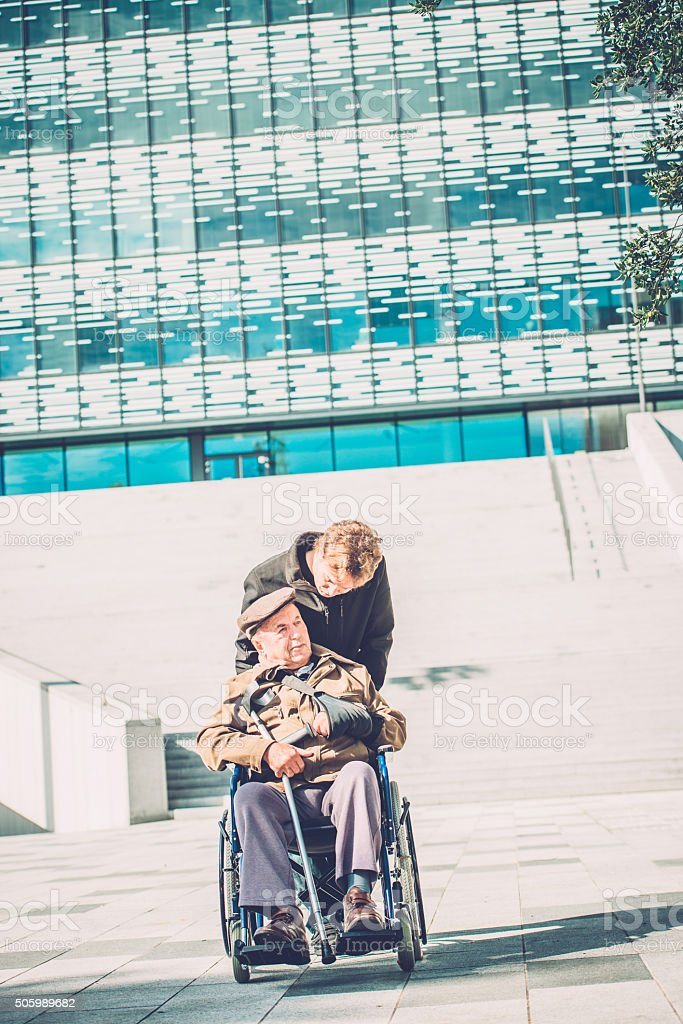 Senior Disabled Man in Wheelchair and Grandson Outdoors, Europe stock photo