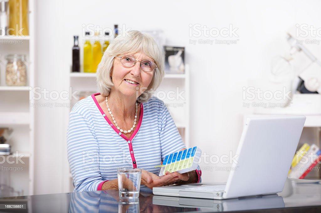 Senior Dispensing Medication From Dorset Box After Checking Details Online stock photo