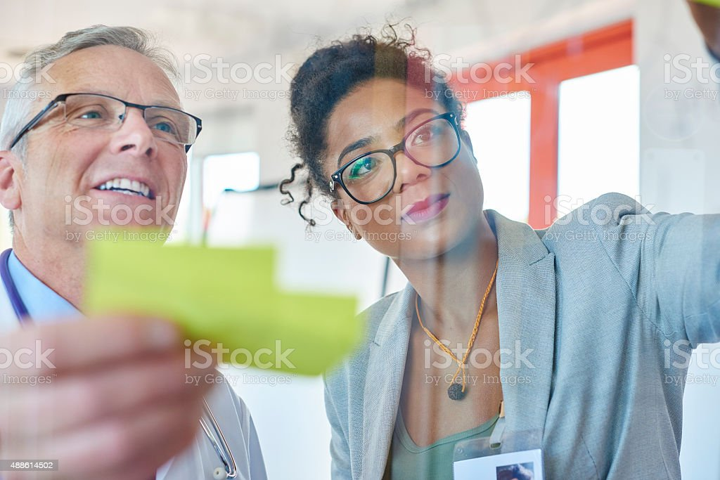 senior doctor and businesswoman brainstorming stock photo