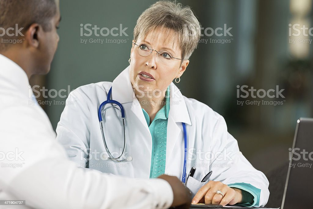 Senior doctor discussing something with colleague in meeting royalty-free stock photo