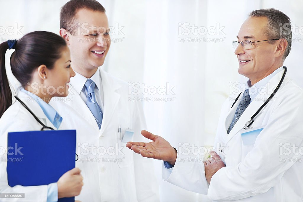 Senior doctor gives advice to younger colleagues. royalty-free stock photo
