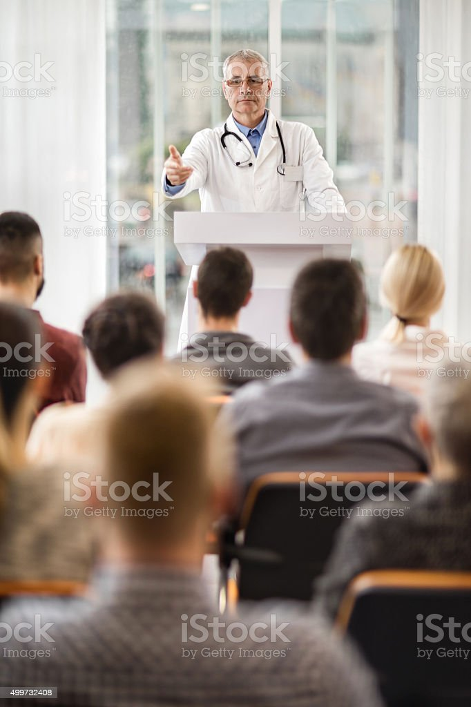 Senior doctor giving a speech on education event. stock photo