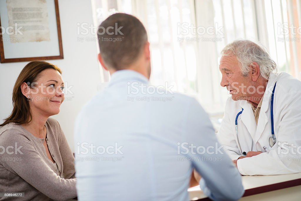 Senior doctor having consultation wit mid-adult couple stock photo