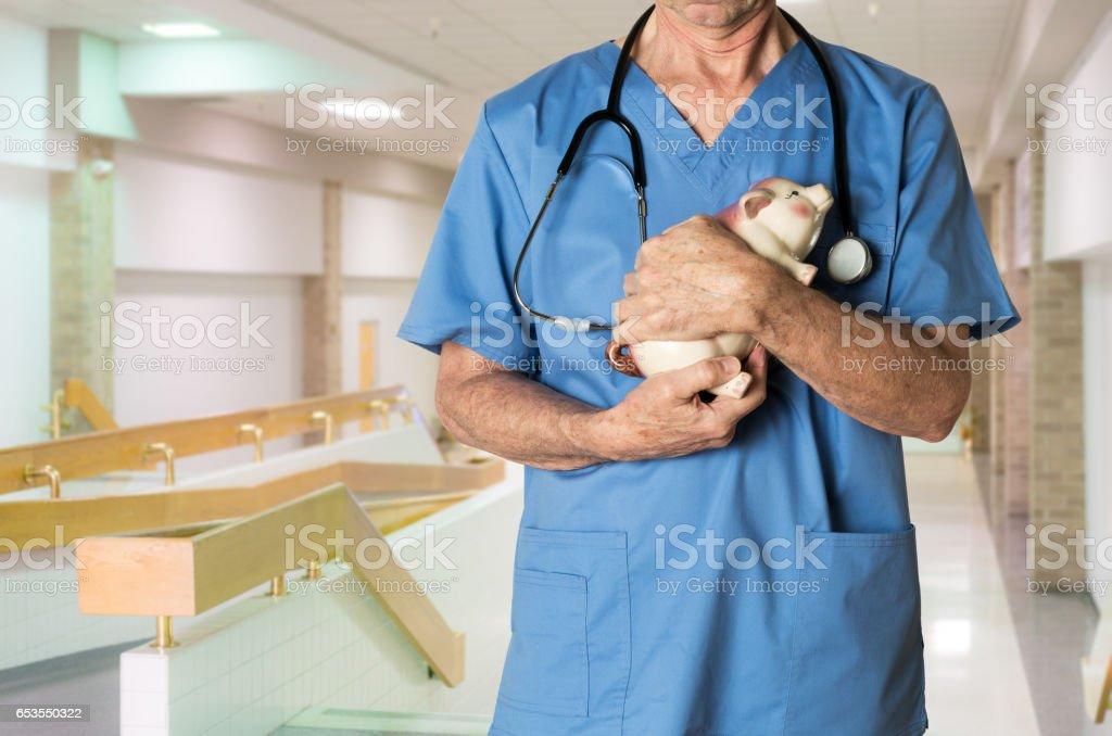 Senior doctor in scrubs with piggybank stock photo