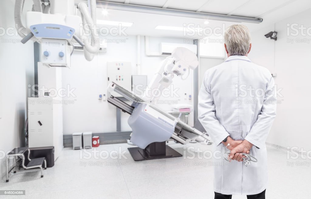 Senior doctor looking at CT scanner in hospital laboratory stock photo