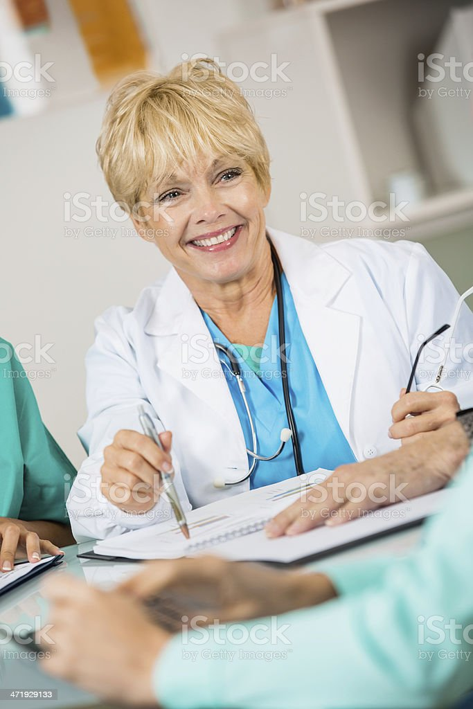 Senior doctor or nurse in hospital staff meeting royalty-free stock photo