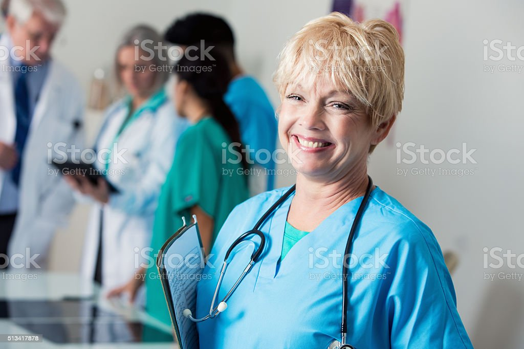 Senior doctor or nurse smiles in staff meeting stock photo