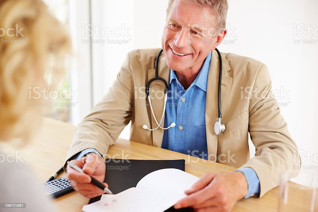 Senior doctor prescribing medicines to a patient royalty-free stock photo