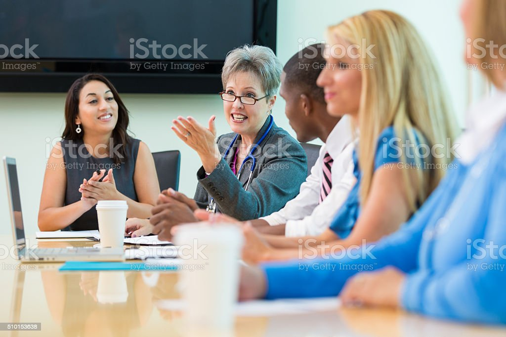 Senior doctor speaks in hospital board meeting stock photo