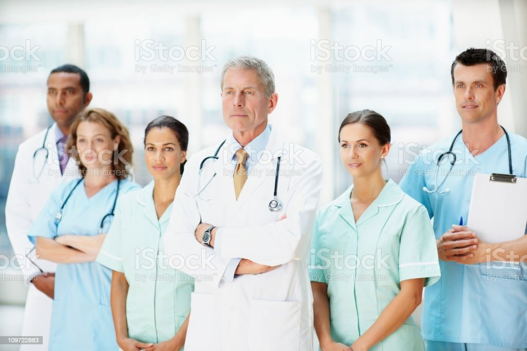 Senior doctor standing with hands folded in front of team royalty-free stock photo
