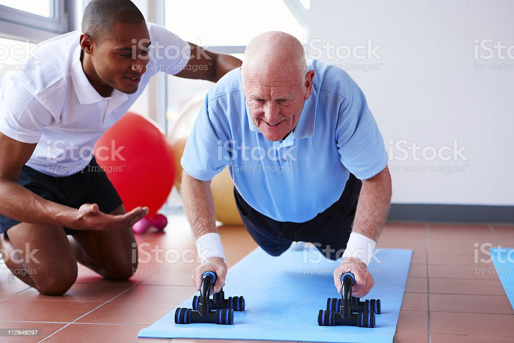 Senior Doing Push-Ups with His Trainer royalty-free stock photo