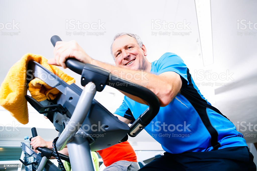 Senior doing sport on spinning bike in gym stock photo