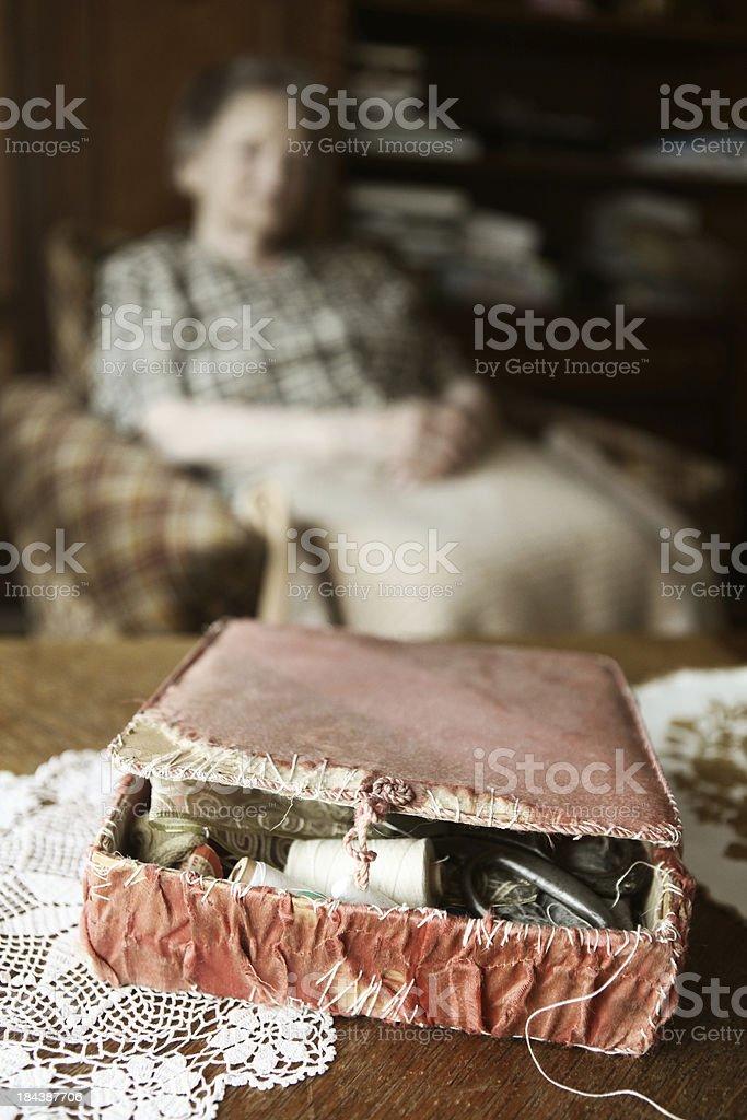 senior dressmaker with her old sewing basket stock photo