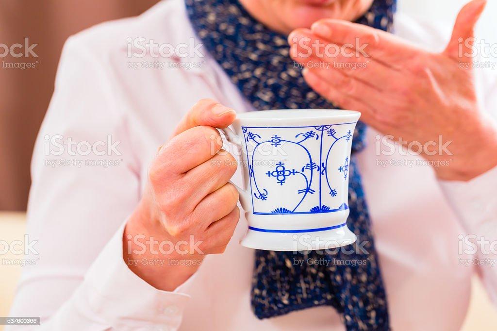Senior drinking tea to cure flu stock photo