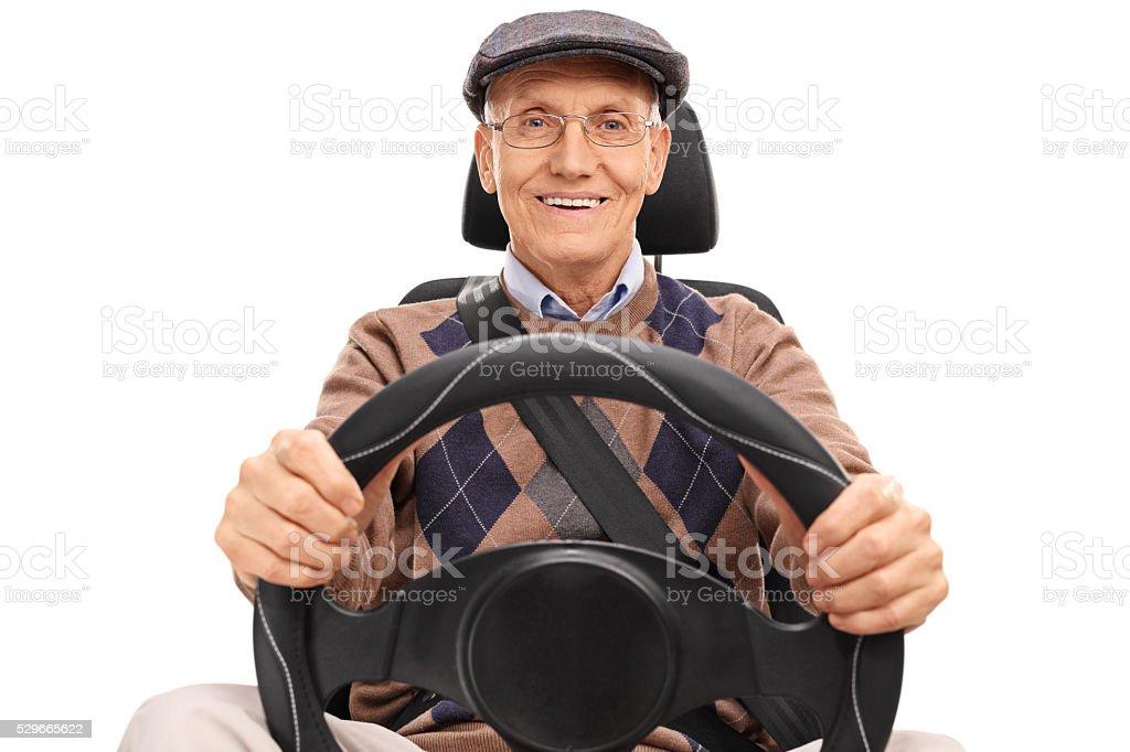 Senior driver holding a steering wheel stock photo
