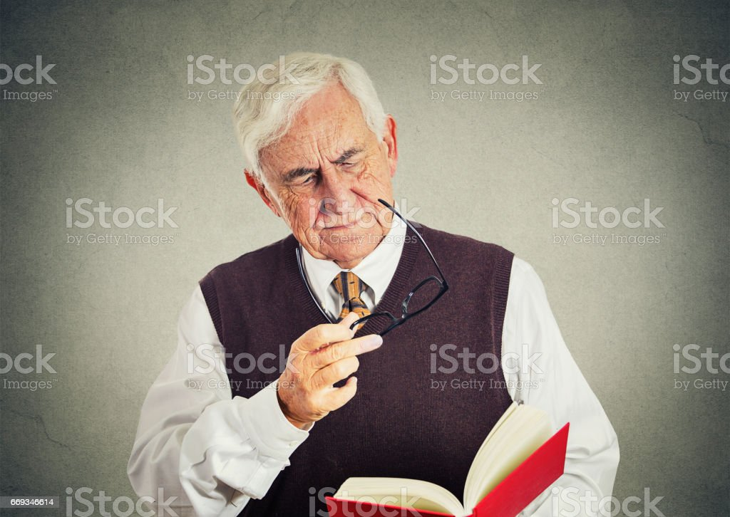 senior elderly man holding book, glasses having eyesight problems unable to read stock photo