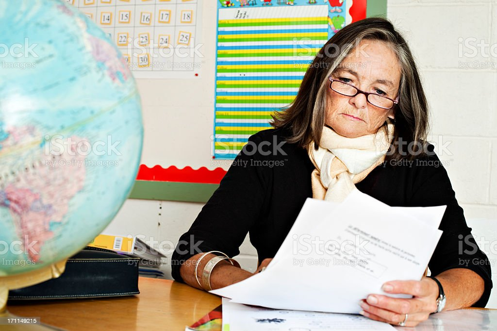 Senior elementary teacher correcting homework stock photo