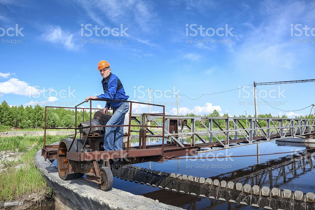 Senior engineer in hardhat standing on waste water treatment unit stock photo