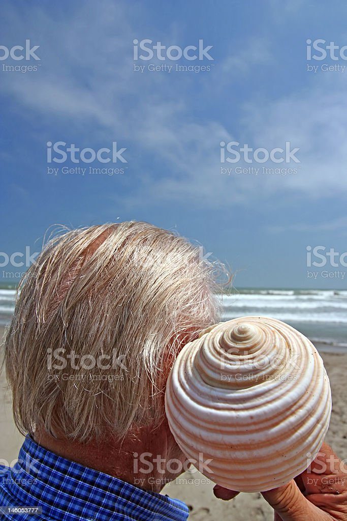 Senior enjoying sound of a shell (up) royalty-free stock photo