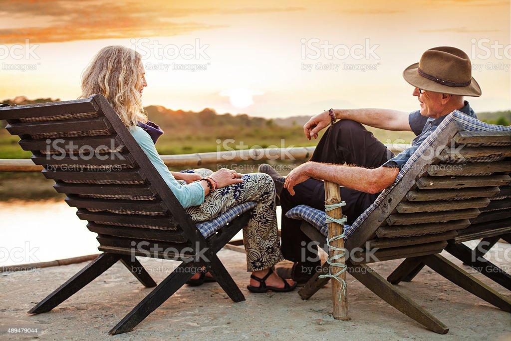 Senior european couple seating on chaise lounge on sunset stock photo