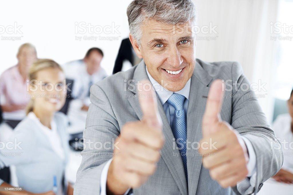 Senior executive in office gesturing good luck sign royalty-free stock photo