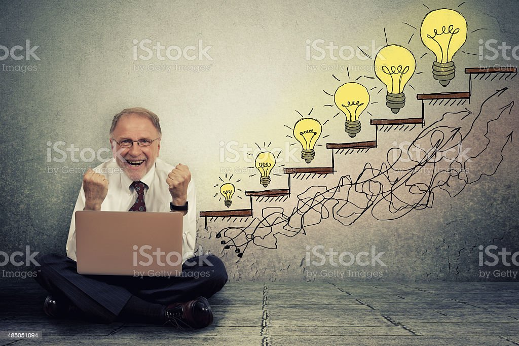 senior executive man working on computer celebrates success stock photo