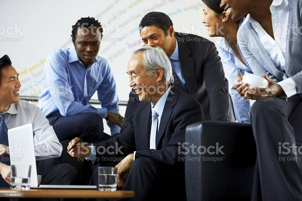 Senior executive viewing proposal on laptop to his colleagues royalty-free stock photo