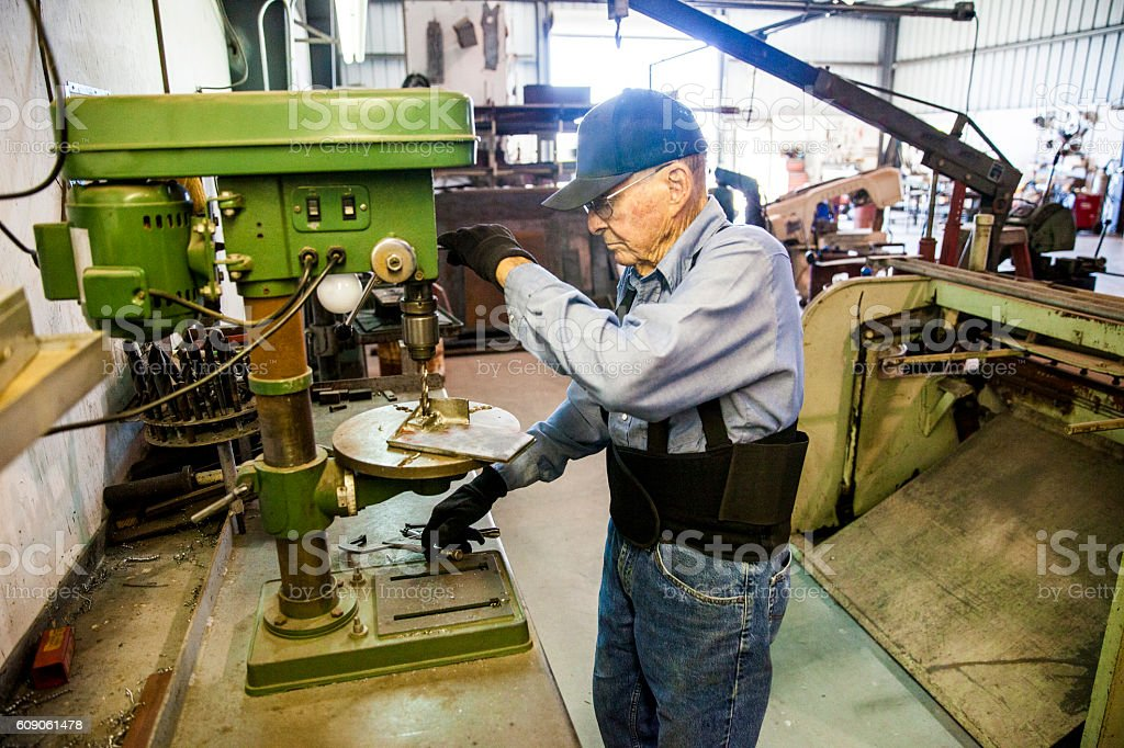 Senior Farmer Man Using Drill Press in Workshop stock photo